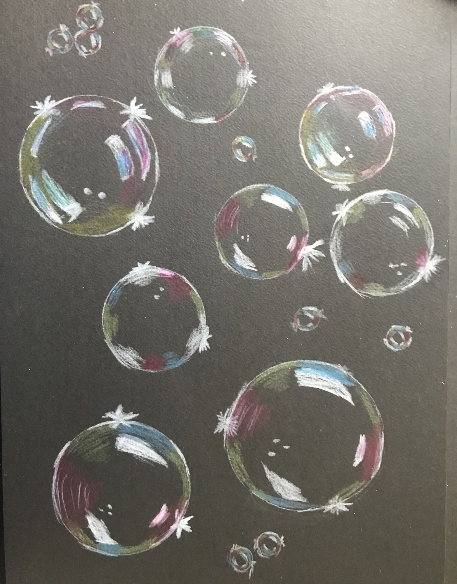 Soap bubbles on a black background. The bubbles have various sizes and contain the colours blue, yellow, pink, green and white.