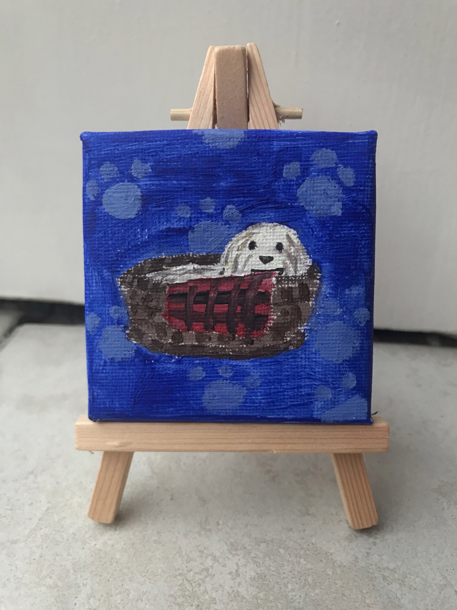 Dog in basket. The dog is a white and grey bearded collie. The basket is brown and made of reed and has a black and red checkered blanket hanging over the edge. The background is dark blue and has light blue paw prints on it. The painting is on a small easel.