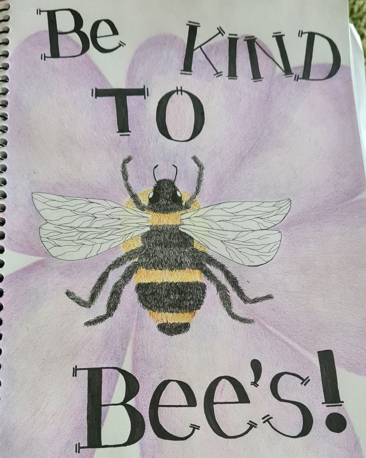 """This is a picture of a light purple flower that takes up the whole page with a bumble bee on top of it. On top of the flower there are the words """" be kind to bees"""" in black lettering."""