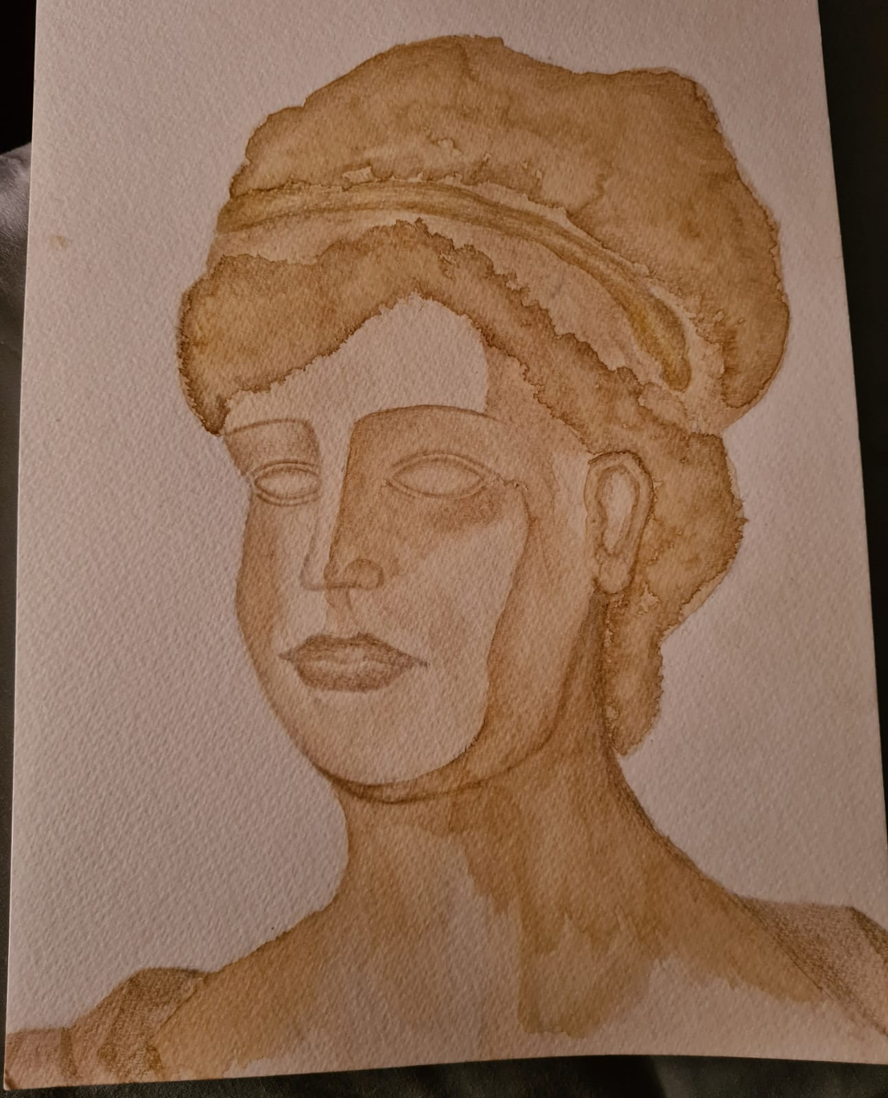This is a picture of a grecian style portrait of a woman. It was painted using tea and coffee which has given it a different shades of light brown throughout the portrait.