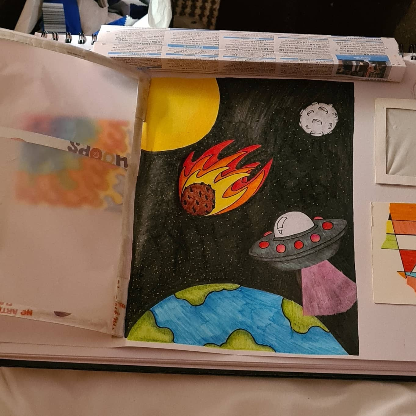 This is a picture of a window scene that has been made out of recycled materials. On the left of the picture their is a small picture with a wavy pattern on it. The colours that are on the picture are purple, light blue, light green, orange, red and yellow. Next to the picture there is a brown cardboard window that has a space scene inside of it, the space scene includes the earth, sun, moon, meteor with flames, alien spaceship and stars. Above the window there is a handmade pull down blind that has been made out of folded newspaper. To the right of the newspaper blind there is a handmade cardboard mirror, below that there is another small picture which is made up of triangular shapes and lines. Some of the shapes have been coloured in using the colours, yellow, light green, red, orange, black, light blue and pink.